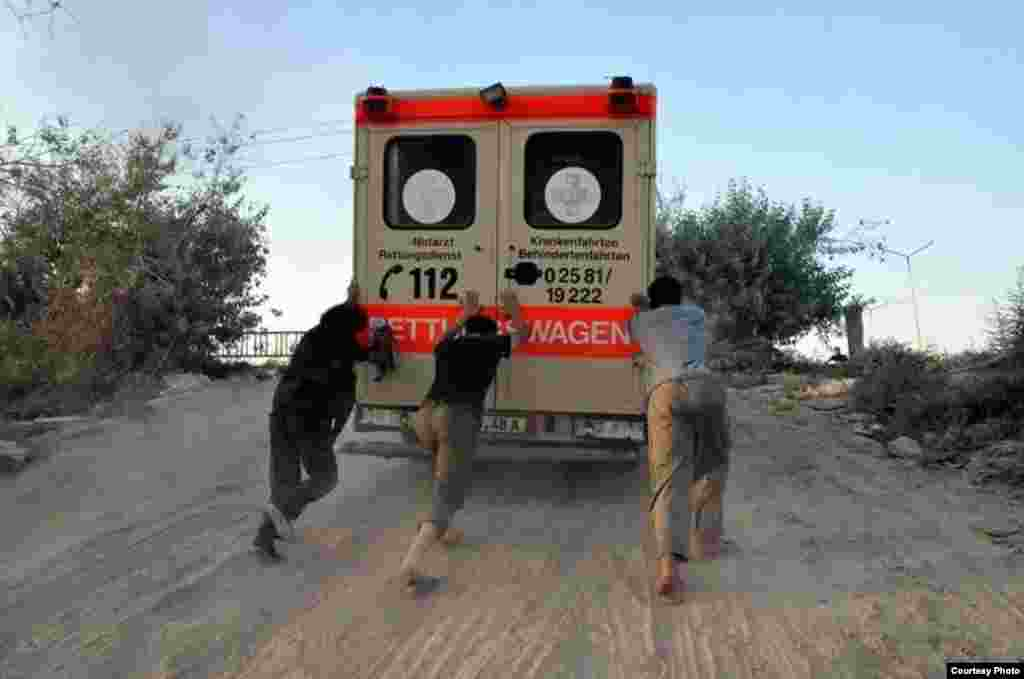 Abdul-Rahman (Peter) Kassig (center) helps push an ambulance up a hill during his time working with SERA. Photo taken near Deir Ezzor, August 2013. (Copyright, with permission to use from Kassig family)