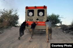 FILE - Abdul-Rahman (Peter) Kassig (center) helps push an ambulance up a hill during his time working with SERA. Photo taken near Deir Ezzor, August 2013. (Copyright, with permission to use from Kassig family)
