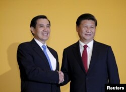 FILE - Chinese President Xi Jinping shakes hands with Taiwan's President Ma Ying-jeou during a summit in Singapore November 7, 2015.