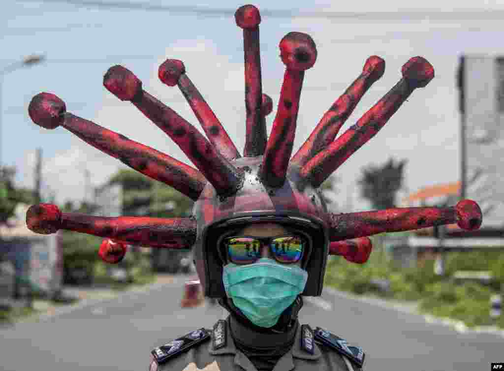 An Indonesian police officer wearing a COVID-19 coronavirus themed helmet conducts a campaign and disinfects motorists' vehicles in Mojokerto, East Java.