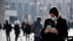 Žena nosi zaštitnu masku dok gleda u svoj telefon, Milan, Italija, 24. februar 2020.