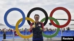 La triathlète Gwen Jorgensen des États-Unis pose avec sa médaille d'or aux Jeux olympiques d'été de 2016 à Rio de Janeiro, le 20 août 2016. REUTERS/Jeff Pachoud/Pool