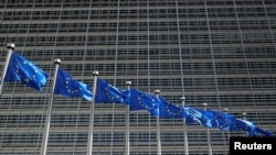 FILE - European Union flags flutter outside the EU Commission headquarters in Brussels, Belgium June 20, 2018.