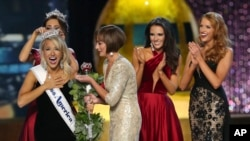 The outgoing Miss America, Betty Cantrell, back left, crowns the Miss America winner Miss Arkansas Savvy Shields, while Lynn Weidner, third right, assists, as Miss Maryland Hannah Brewer, second right, and Miss Texas 2016 Caroline Carothers, look on durin