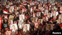 Para anggota Muslim Brotherhood dan pendukung presiden terguling Mohamed Morsi memegang posternya menyusul pernyataan kudeta dari militer (3/7).