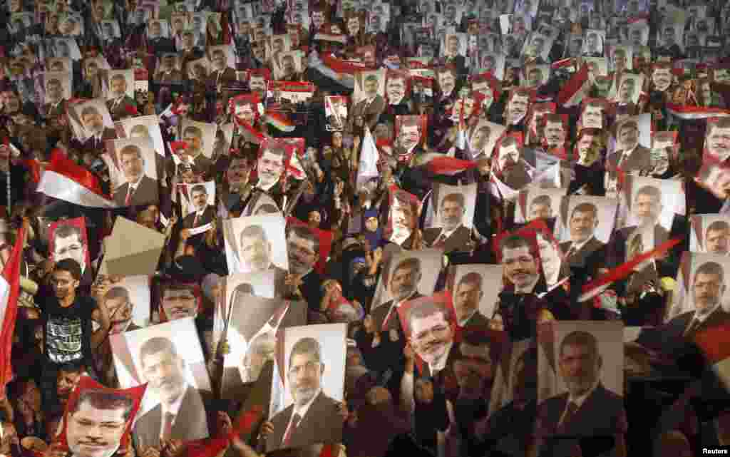 Members of the Muslim Brotherhood and supporters of Egypt's President Mohamed Morsi hold pictures of him as they react after the army's statement was read out on state TV, at the Raba El-Adwyia mosque square in Cairo, July 3, 2013. Egypt's armed forces overthrew elected Islamist President Morsi and announced a political transition with the support of a wide range of political, religious and youth leaders.