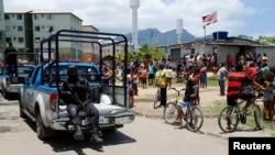 Des habitants regardent un policier passé lors d'une opération anti-drogues dans la favela de la Cité de Dieu à Rio de Janeiro, Brésil, le 20 novembre 2016.