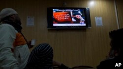 FILE - People watch a TV news report about the leader of the Pakistani Taliban, Mullah Fazlullah, at a coffee shop in Islamabad, Pakistan, Nov. 7, 2013.