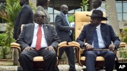 FILE - In thisApril 29, 2016 file photo, South Sudan's then-First Vice President Riek Machar, left, looks across at President Salva Kiir, right, as the two sit to be photographed following the first meeting of a new transitional coalition government, in the capital Juba, South Sudan.