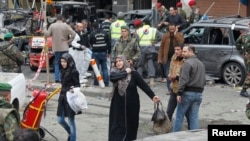Women walk past as Lebanese army soldiers, gather at the site of Tuesday's explosion, in the Haret Hreik area in the southern suburbs of the Lebanese capital Beirut, Jan. 22, 2014.
