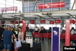 Para penumpang antre di loket Virgin Australia Airlines di Bandara Internasional Kingsford Smith, Sydney, Australia, di tengah pandemi Covid-19, 18 Maret 2020.