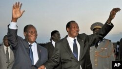 Ivory Coast President Alassane Ouattara (L) greets president Blaise Compaore of Burkina Faso at Yamoussoukro airport, a day ahead of his inauguration, May 20, 2011