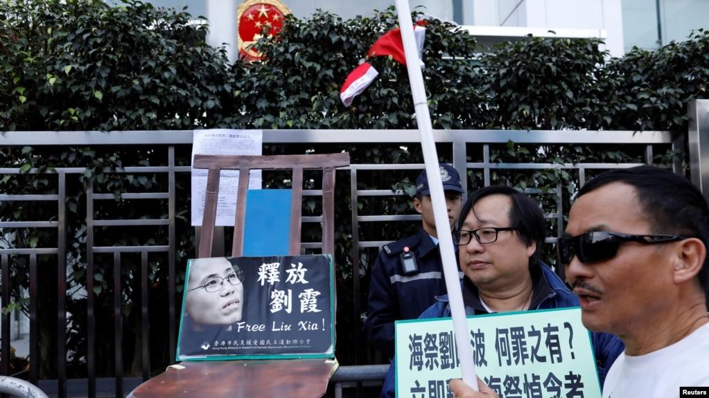 资料照 香港抗议者在圣诞节在中联办前摆放一张空椅子和刘晓波遗孀刘霞的照片,呼吁中国当局解除对刘霞的软禁。(2017年12月25日)