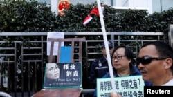 香港抗议者在圣诞节在中联办前摆放一张空椅子和刘晓波遗孀刘霞的照片,呼吁中国当局解除对刘霞的软禁。(2017年12月25日)