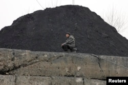 FILE - A North Korean man sits beside a pile of coal on the bank of the Yalu River in the North Korean town of Sinuiju.