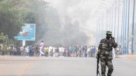 Malijski vojnik kraj zapaljene barikade ispred logora pobunjene padobranske jedinice u Bamaku
