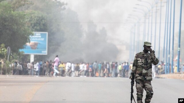 A soldier patrols near a burning road block outside the paratrooper camp, home of the former president's Red Beret presidential guard, in Bamako, February 8, 2013.
