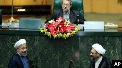 El nuevo presidente de Irán, abajo a la izquierda en la foto, arriba al podio para su investidura de juramento que fue tomado por el presidente de la Corte de Justicia iraní, Sadeq Larijani, a la derecha, este domingo en Teherán.