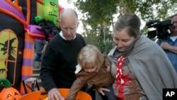 El exgobernador Jerry Brown ayuda a Abigail Cacciatore, de 2 años, a seleccionar su regalo de Halloween mientras hace un truco o trato en Sacramento, California.