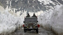 Indian army soldiers travel in a vehicle on a mountainous road covered by snow after the Srinagar-Leh highway was opened to traffic in Zojila, 108 km (67 miles) east of Srinagar April 25, 2012. The 443 km (275 miles) long highway was opened by Indian army