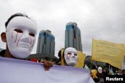 Para wartawan Indonesia mengenakan topeng saat mengikut pawai Hari Buruh di Museum Nasional (Monas), Jakarta, 1 Mei 2019. (Foto: Reuters)