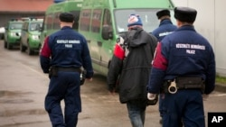 FILE - A migrant is seen escorted past police vehicles at a detention center for illegal migrants, in Szeged, southern Hungary, Dec. 17, 2014.