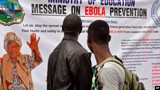 FILE - Liberian President Ellen Johnson Sirleaf appears on a banner warning people about the Ebola virus in Monrovia, Aug. 8, 2014.