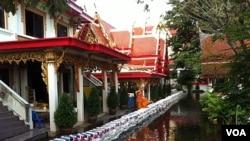 Biksu Thailand mengamati air tergenang dan membanjiri kuil Sai Mai di pinggiran utara kota Bangkok (19/10).