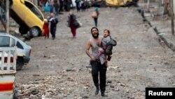 이라크 정부군과 이슬람 극단주의 무장단체 IS의 교전이 발생한 모술에서 지난 3월 어린 딸을 안고 IS 진영에서 정부군 진영으로 이동하는 남성이 울음을 터트리고 있다.