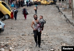 FILE - A man cries as he carries his daughter while walking from an Islamic State-controlled part of Mosul toward Iraqi special forces soldiers during a battle in Mosul, Iraq, March 4, 2017.