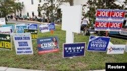 佛羅里達州拉哥市選舉辦公室投票站外排隊提前投票的選民和路邊插著的競選宣傳牌。(2020年10月21日)
