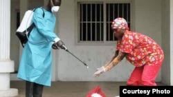 Un employé de la Croix-Rouge libérienne désinfecte les mains d'une personne suspectée d'avoir touché un malade d'Ebola, Monrovia, septembre 2014. (Crédit: alerte internationale)