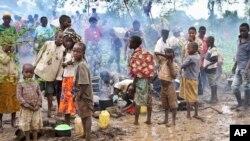 Des enfants burundais réfugiés au Rwanda se tiennent dans la boue près de leurs tentes au camp de Gashora dans le district de Bugesera, (au Rwanda), le 24 avril 2015.