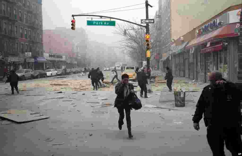 Pessoas fogem reagindo à explosão que destruiu dois prédios em Harlem, Nova Iorque, Março 12, 2014.