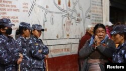 FILE - A devotee looks towards police personnel as she offers prayers at the premise of the Boudhanath Stupa in Kathmandu.