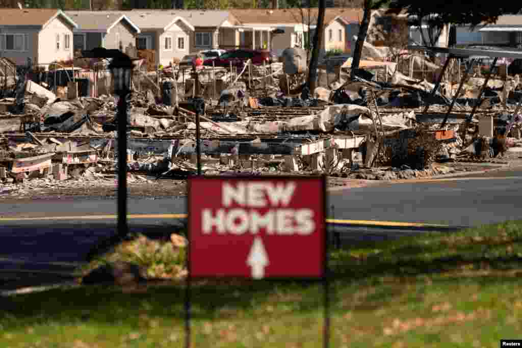 A sign advertising new homes stands in a neighborhood severely damaged by wildfire in Medford, Oregon, Sept. 20, 2020.