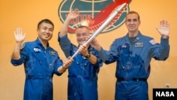 Los tripulantes de la expedición 38, el ingeniero de vuelo japonés Koichi Wakata, el comandante ruso del cohete Soyuz, Mikhail Tyurin y el ingeniero de vuelo estadounidense de la NASA Rick Mastracchio, posan con la antorcha Olímpica previo a su partida.