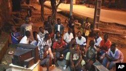 A group of young men watch the announcement of final provisional presidential election results shortly after midnight on the streets of a closed-up Bouake, in northern Ivory Coast, 04 Nov 2010