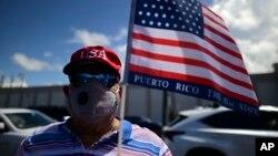 အေမရိကန္အလံနဲ႔ အမ်ိဳးသားတဦးကို Puerto Rico ျပည္နယ္ Carolina ႏိုင္ငံမွာ ေတြ႔ရ။ (ေအာက္တိုဘာ ၁၈၊ ၂၀၂၀)