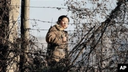 A North Korean female soldier stands watch along the bank of the Yalu River, the China-North Korea border river, near North Korea's town of Sinuiju, 25 Nov 2010