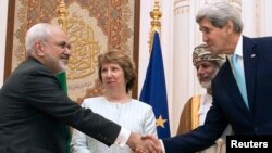 U.S. Secretary of State John Kerry (R) and Iranian Foreign Minister Javad Zarif (L) shake hands as Omani Foreign Minister Yussef bin Alawi (2nd R) and EU envoy Catherine Ashton watch in Muscat Nov. 9, 2014.