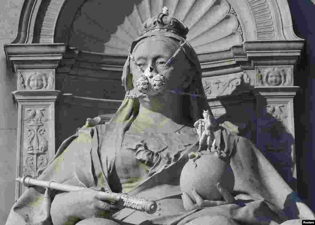 A depiction of a gas mask placed by environmental protest group Greenpeace is seen on a statue of Britain's Queen Victoria near Buckingham Palace in London, Britain.