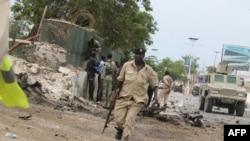 Petugas keamanan Somalia memeriksa lokasi serangan di sekitar gedung parlemen di Mogadishu (24/5).