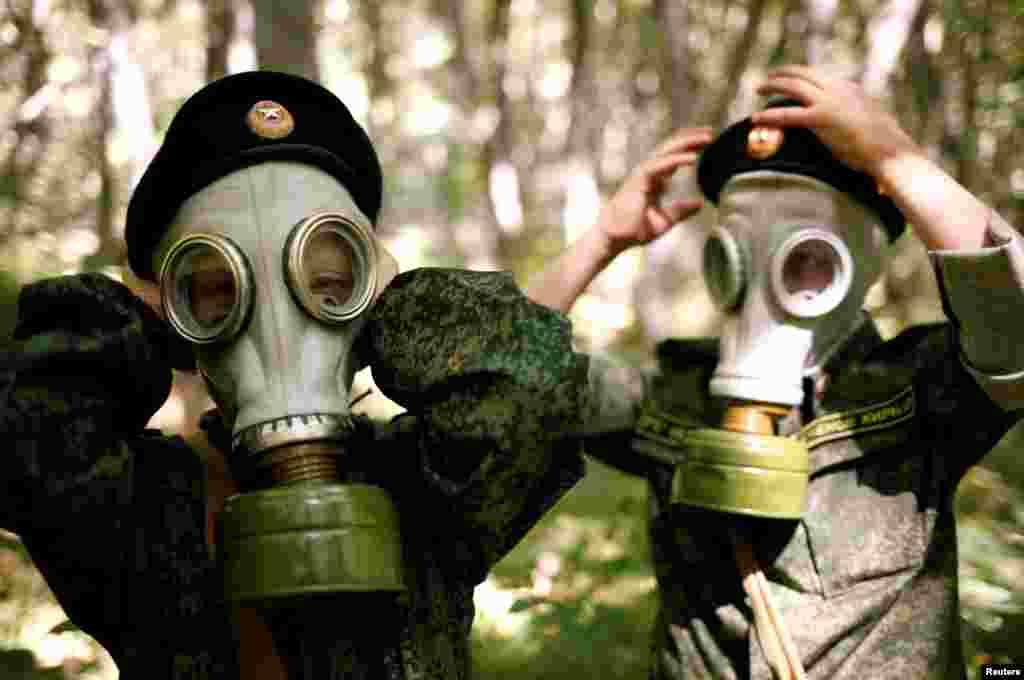 Estudantes da quinta classe da Academia de Cadetes General Yermolov Cadet na Rússia aprendem a colocar máscaras anti-gás.