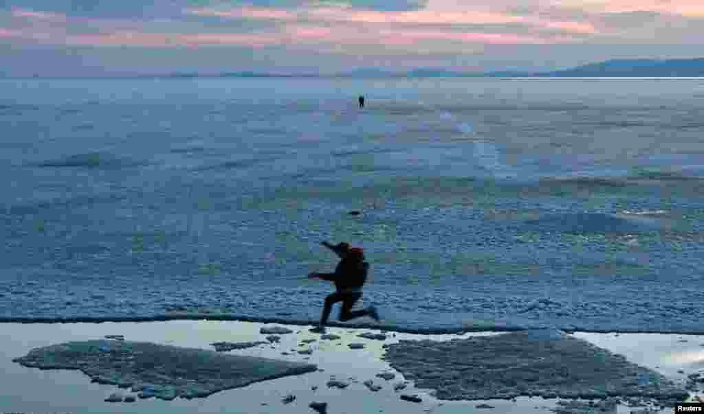 A teenager jumps from floe to floe during an ice drift in Amur Bay in the far eastern city of Vladivostok, Russia.