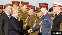 FILE - Iraqi Prime Minister Haider al-Abadi, second from left, shakes hands with military officials with Iraq Defense Minister Khaled al-Obeidi, left, during the Iraqi Army Day anniversary celebration, in Baghdad, Jan. 6, 2015.