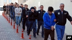 In this photo taken on April 26, 2017, Police officers escort people, arrested because of suspected links to U.S.-based cleric Fethullah Gulen, in Kayseri, Turkey.