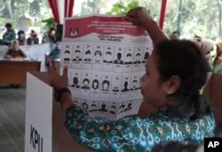 Seorang perempuan memperlihatkan contoh surat suara pemilu legislatif dalam simulasi yang digelar Komisi Pemilihan Umum di Jakarta, 10 April 2019.