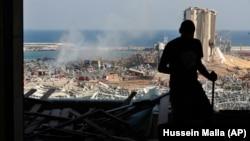 Građanin Bejruta kroz prozor oštećene zgrade gleda ka luci gdje se dogodila velika eksplozija 4. avgusta 2020.