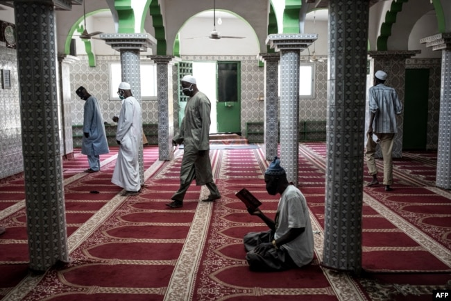 Muslim worshippers take their places whilst adhering to social distancing measures before prayer as Mosques open for the first time after two months in Dakar on May 12, 2020.